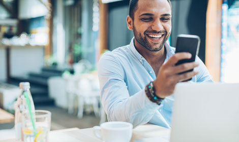 Person smiling looking at mobile in front of a laptop in a restaurant