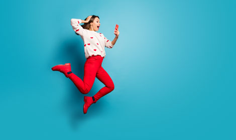 woman jumping excited looking at mobile