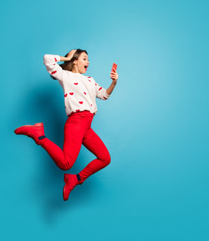 woman jumping excited looking at mobile 303x350