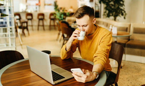 man drinking coffee working on laptop and mobile 470x280
