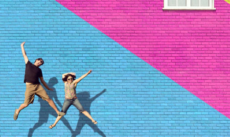 happy people jumping in front of multi-color brick wall 470x280