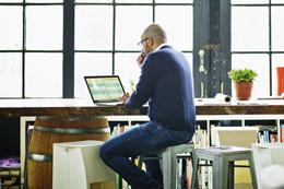 Man sitting at desk with laptop doing data analysis 260x173