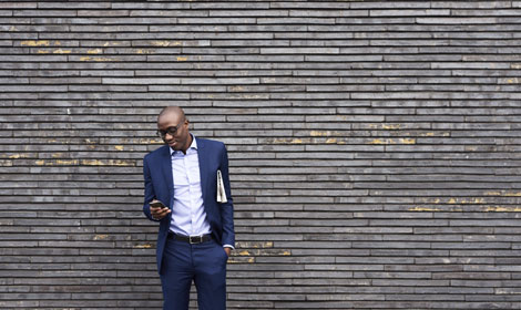 man using mobile phone leaning against wall 470x280