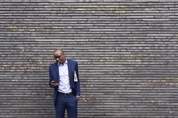 man using mobile phone leaning against wall 260x173