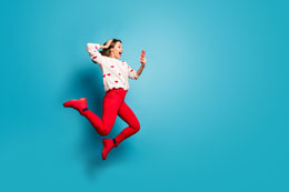 woman jumping excited looking at mobile 260x173