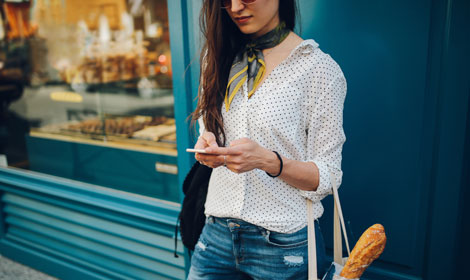 Woman using mobile outside store (470x280px)