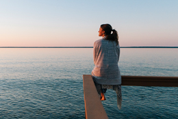 woman sitting on rail over water 260x173