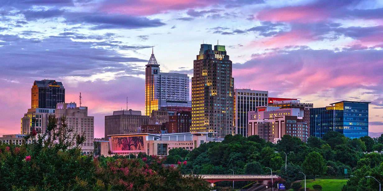 This is a beautiful picture of the Raleigh sky line with a beautiful cotton candy sky