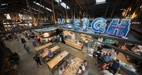 This is a photo of the inside of the Transfer Co. Food Hall. This unique place offers a variety of dining options.