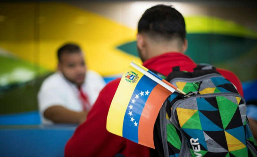 Back of man standing in line with a Venezuelan flag sticking out of his backpack.