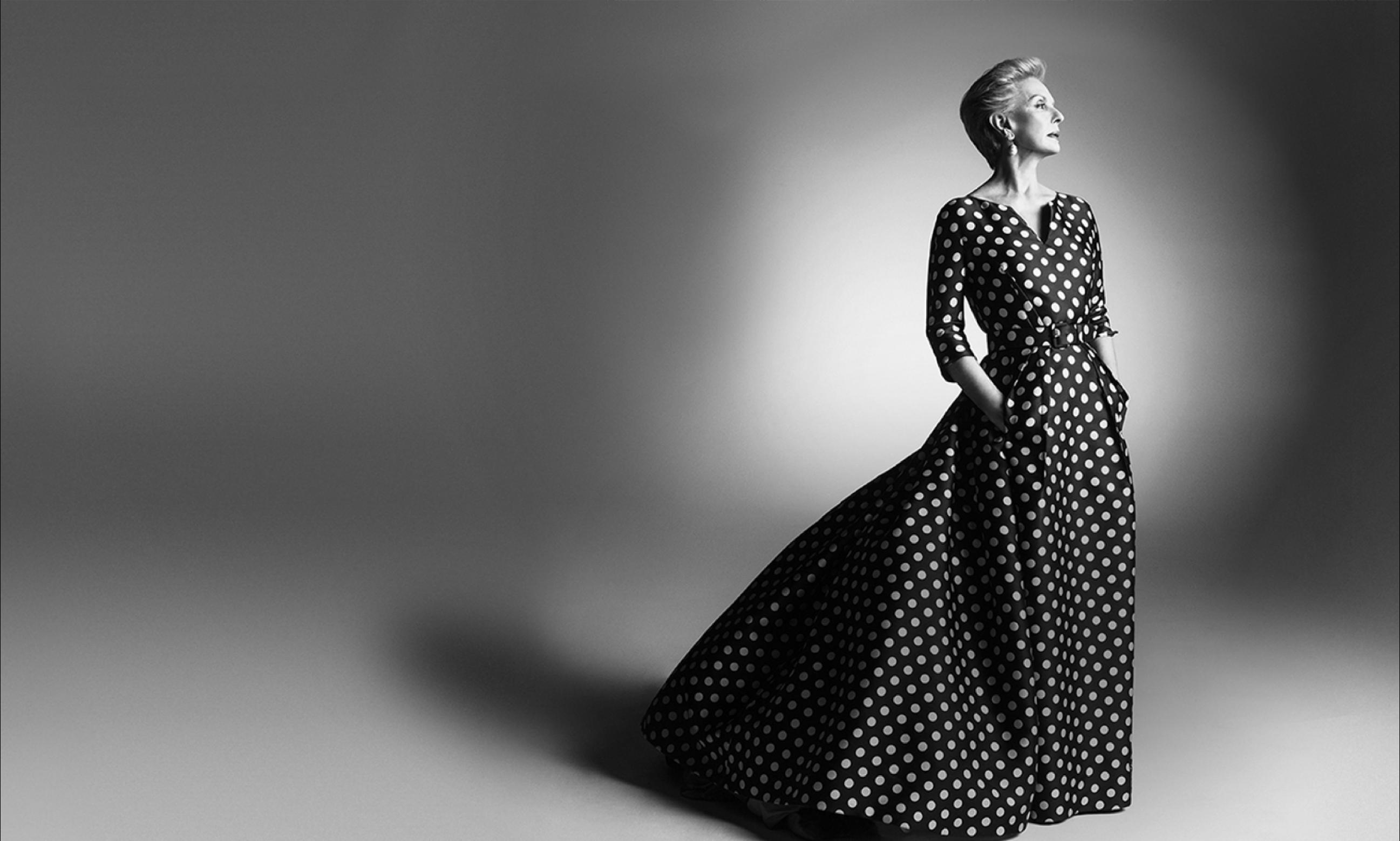 Carolina Herrera standing in beautiful gown.