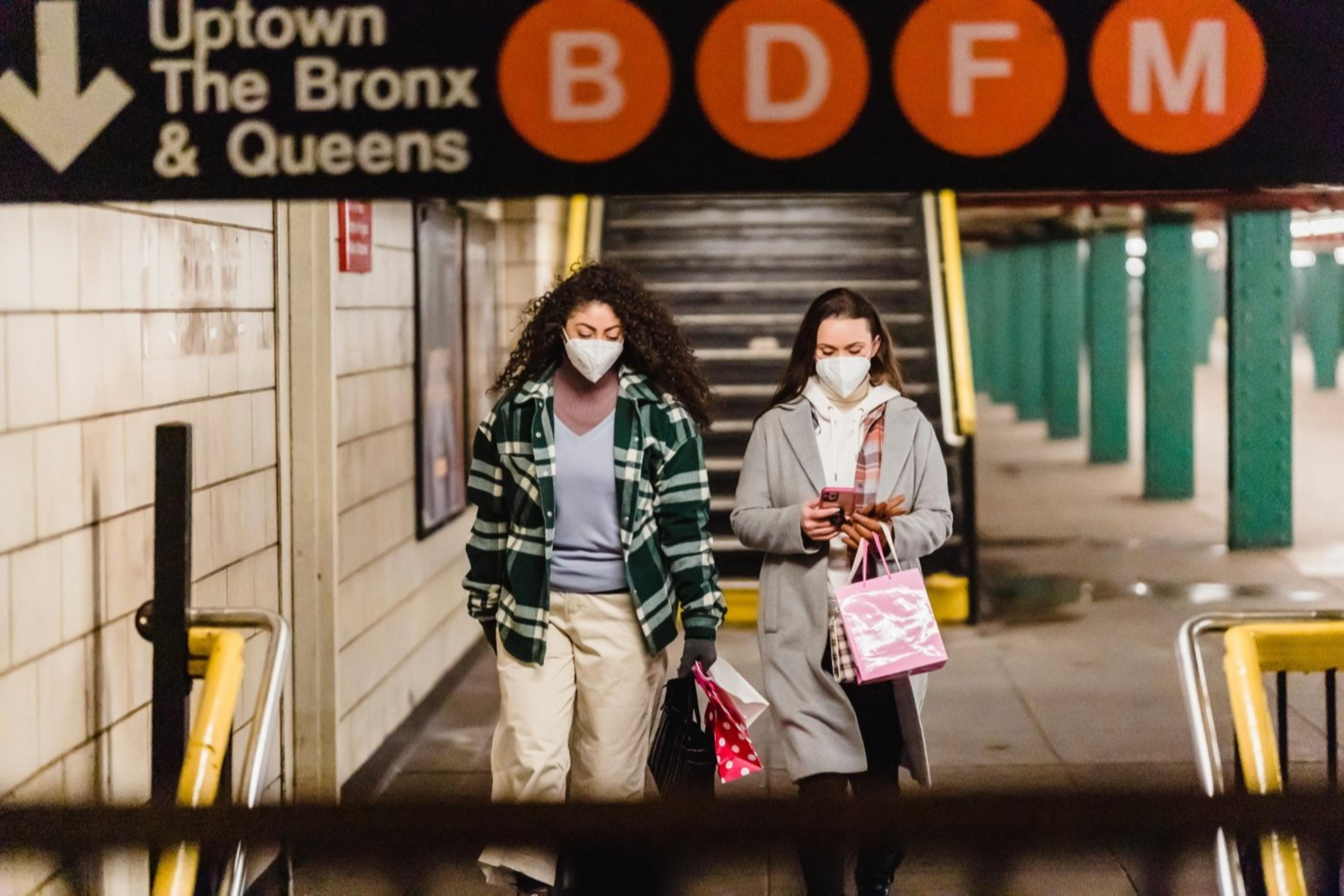 two young woman walking in a subway with face masks on