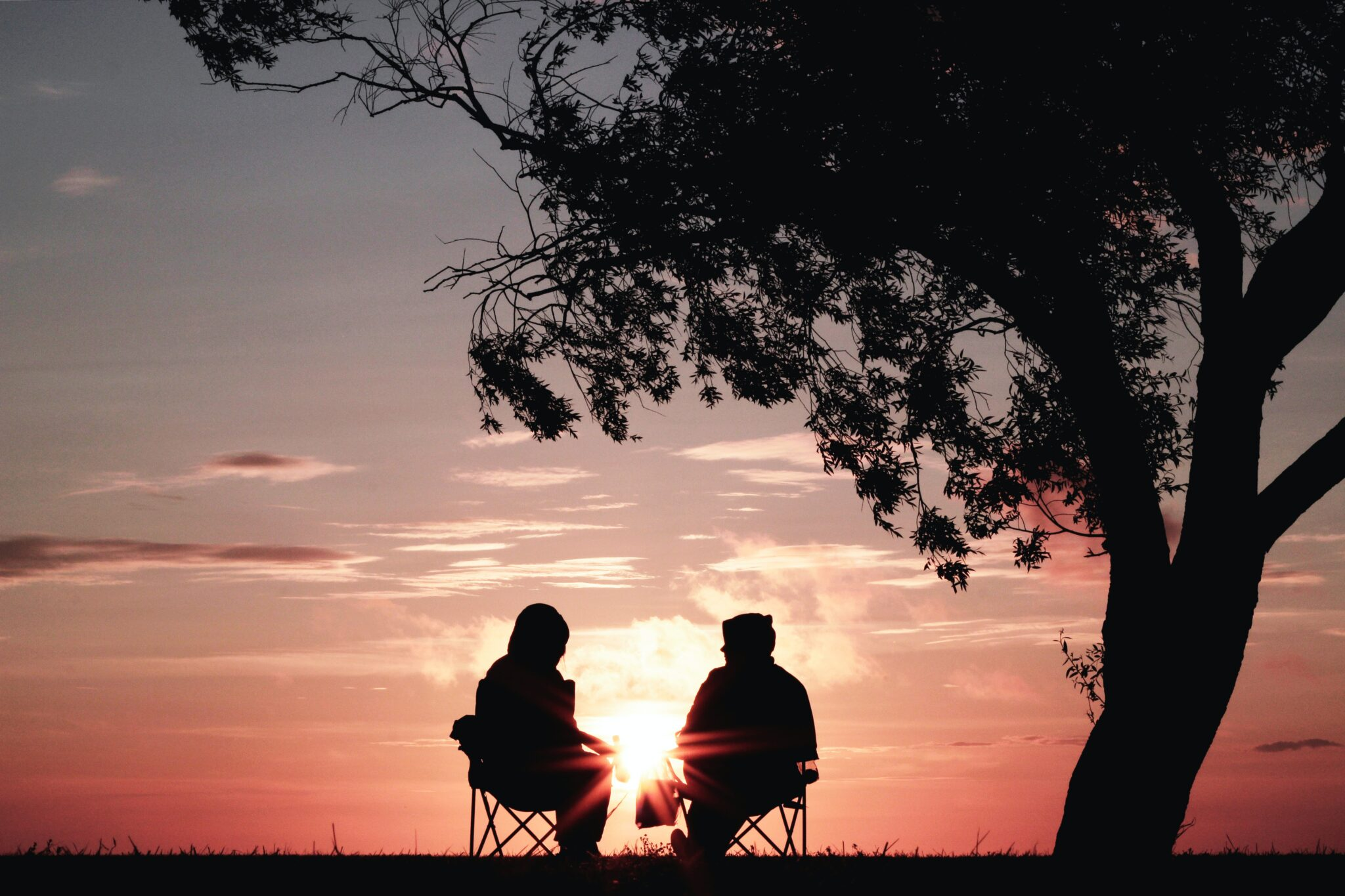 Two people sitting outside, watching the sunset