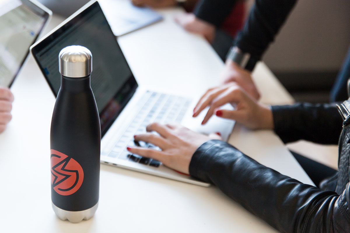 woman on a laptop with a sauce labs water bottle