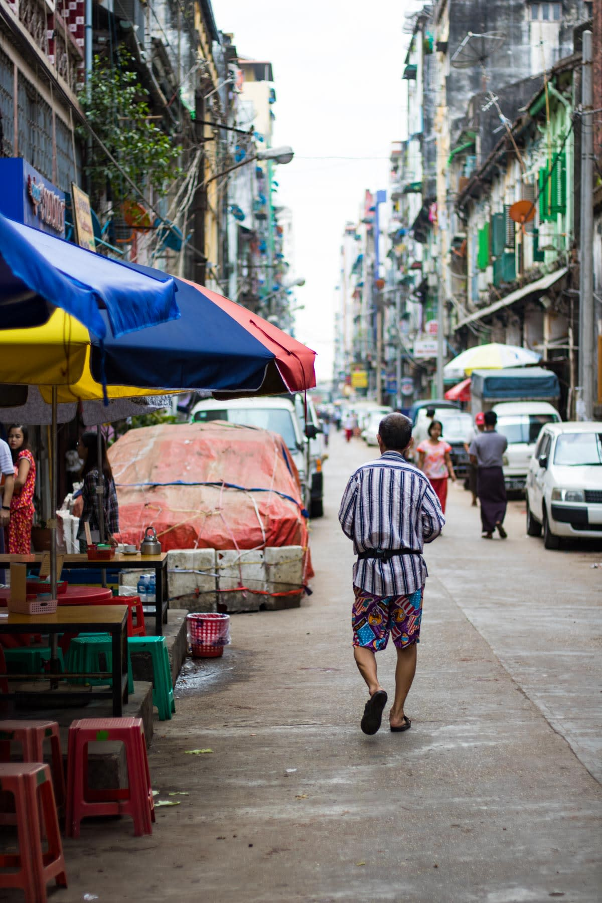Back of a person in stripes walking down a narrow street