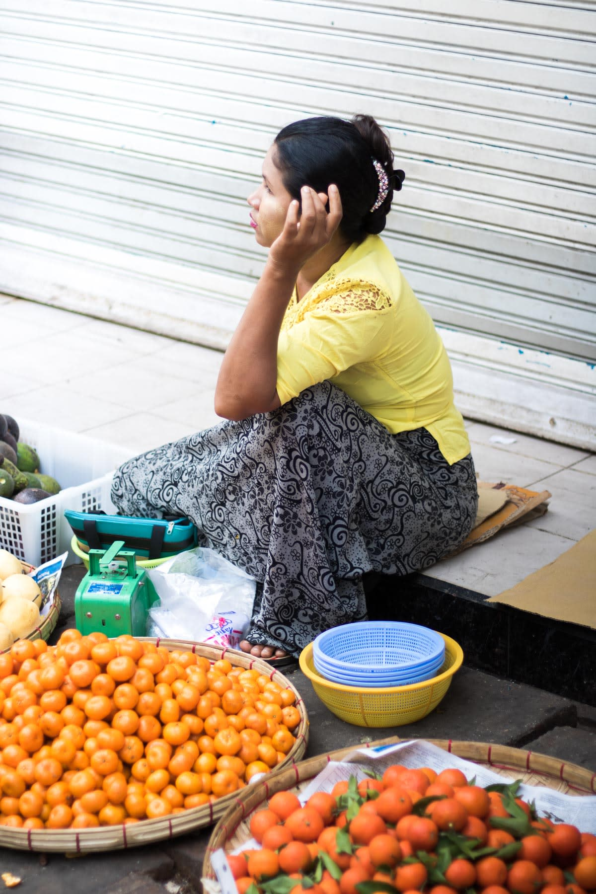 A fruits vendor sitting on curbside with tangerines on display