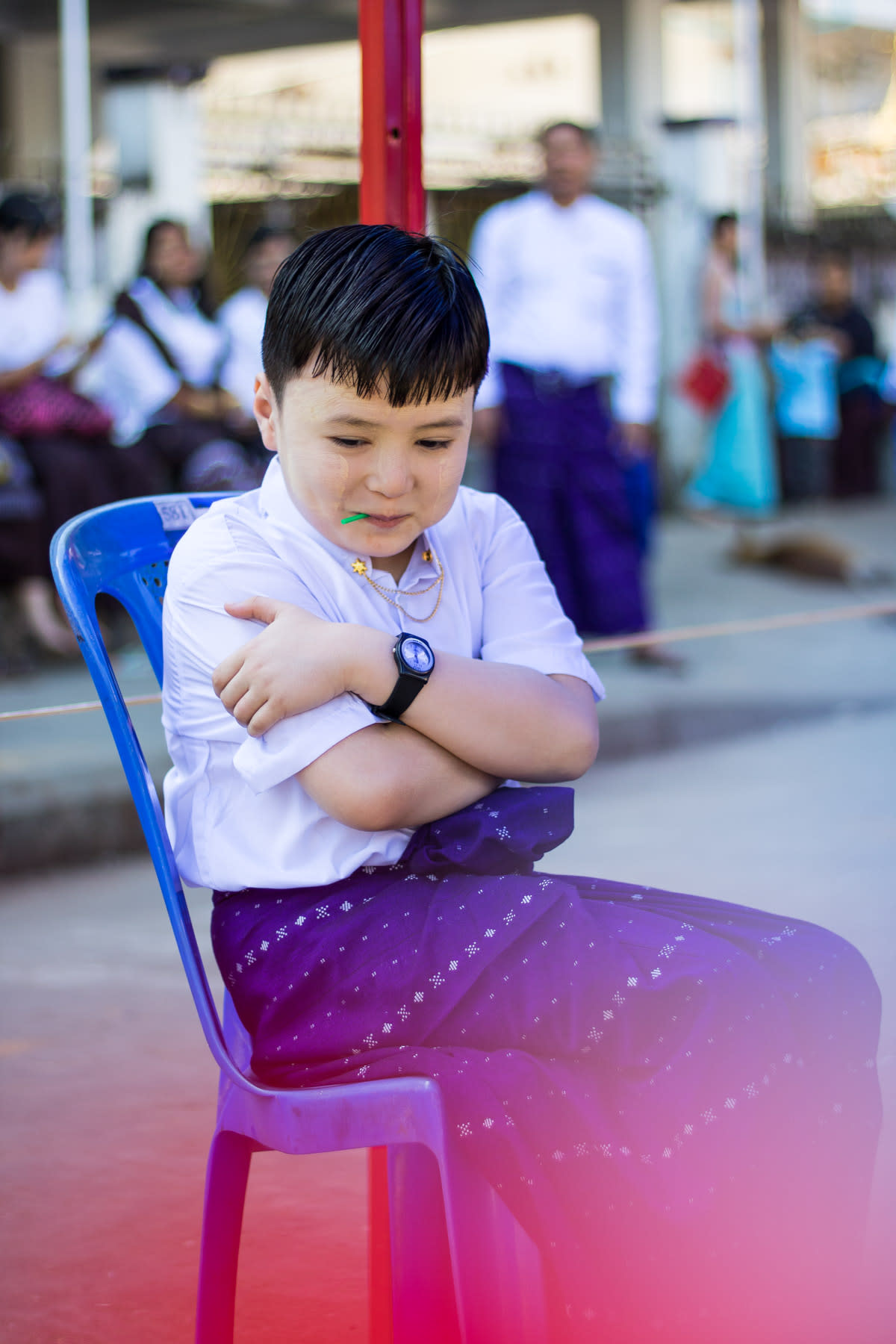 A child sitting on a blue chair with arms crossed