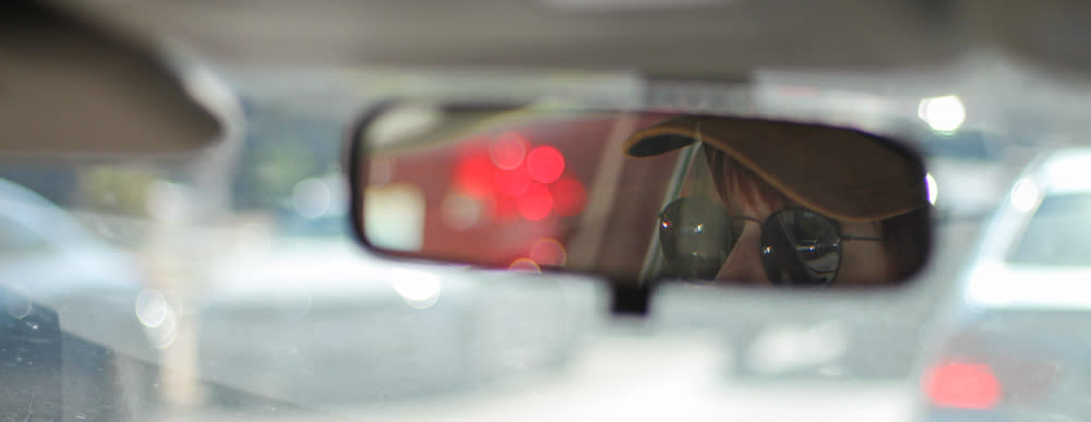 Person with yellow cap and dark sunglasses in view on rear-view mirror