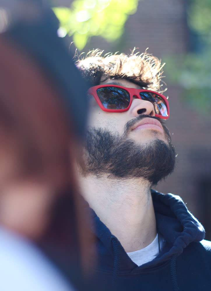 Personal in red-brimmed sunglasses looking up