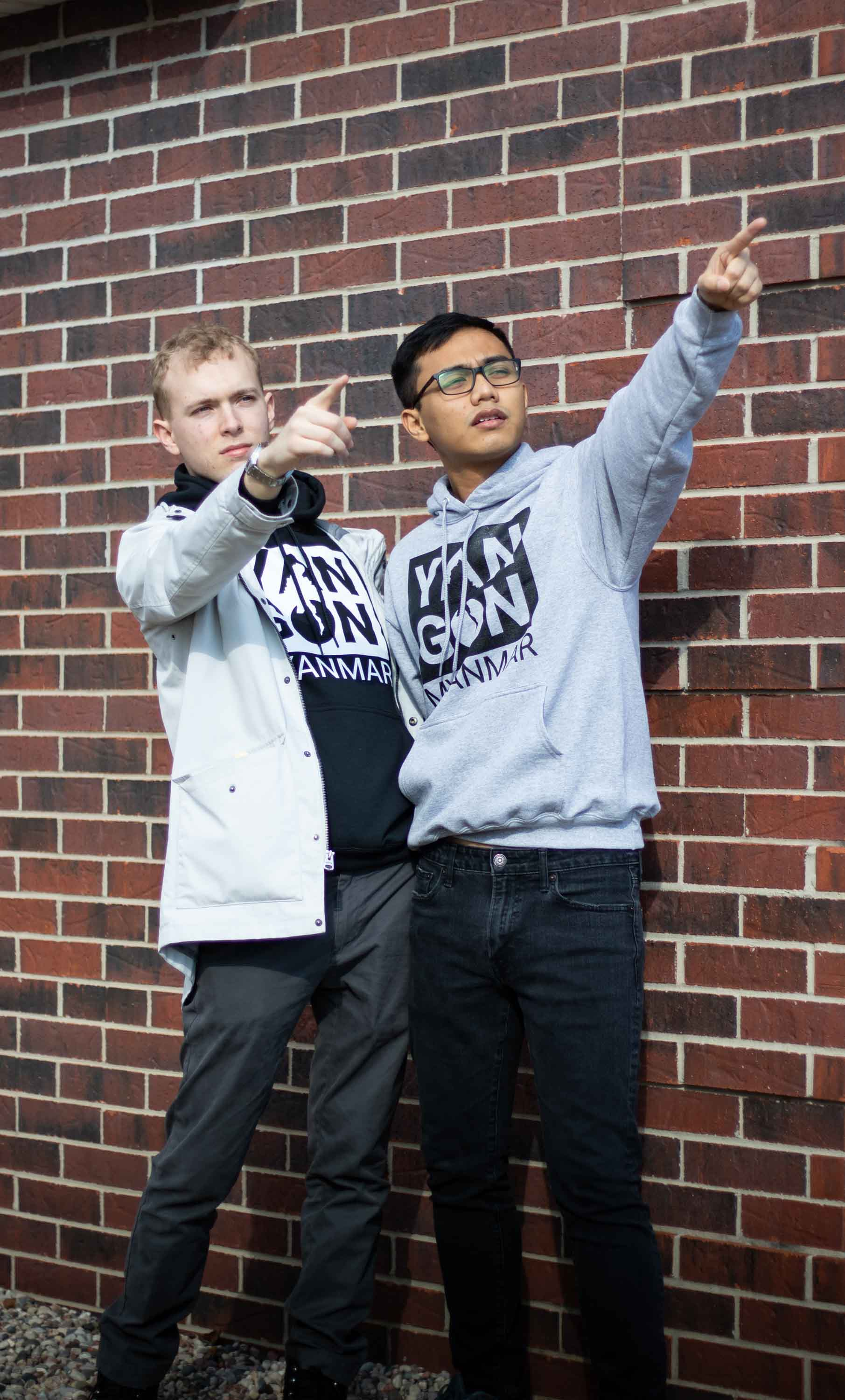 Two men pointing right in front of the bricks