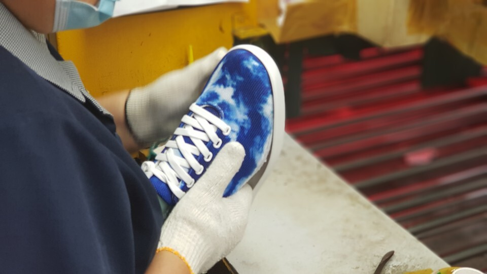 A factory worker in Busan, South Korea attaches the upper to the outsole of the Tie-Dye Blue Atoms.