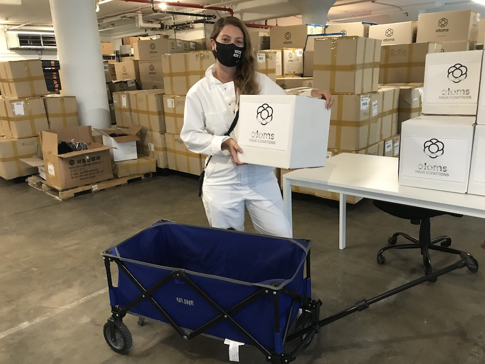 Wide Awakes member Christina Caputo picks up Atoms VOTE NOV 3 masks at the company's Brooklyn Navy Yard office.