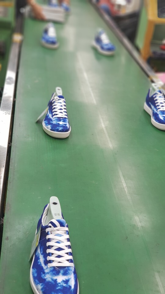 Atoms Tie-Dye Blue sneakers on the conveyer belt in our South Korean factory.