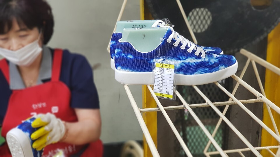 A factory worker checks the Atoms Tie-Dye Blue sneakers.