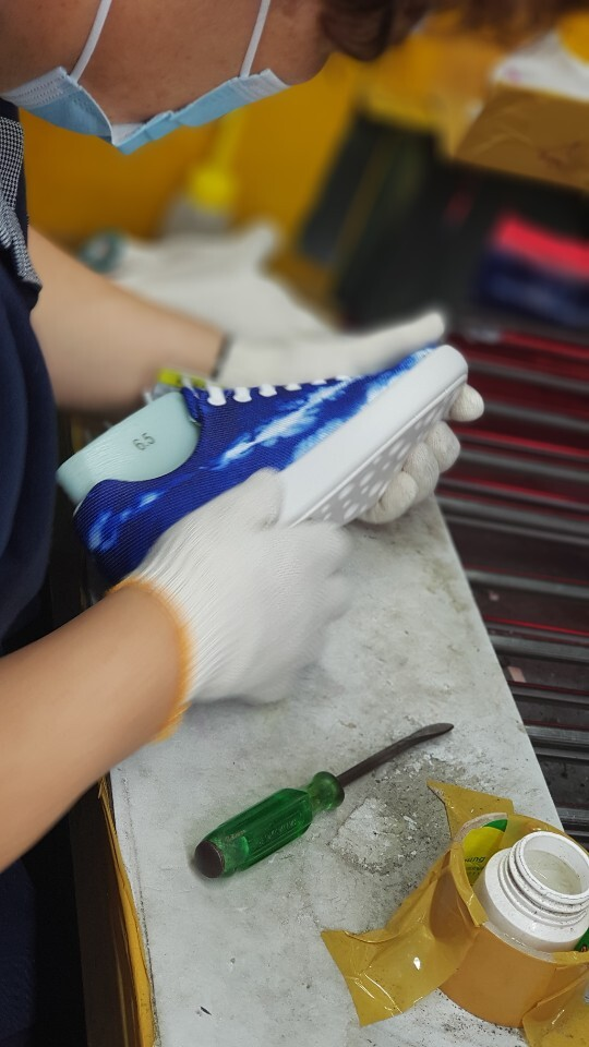 A factory worker checks for quality on the Atoms Tie-Dye Blue sneaker.