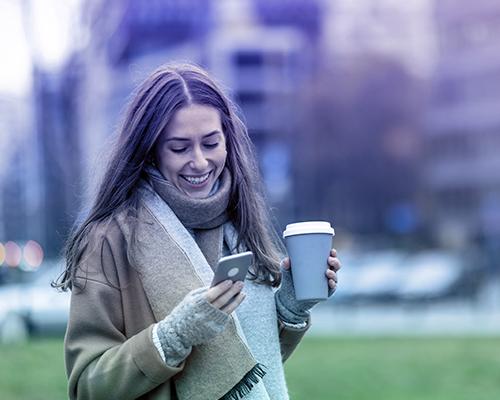 Frau mit Kaffeebecher schaut auf ihr Smartphone