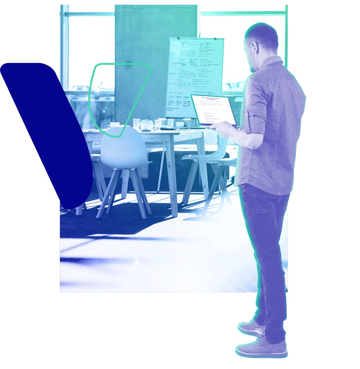 Junger Akademiker steht mit Laptop im Büro