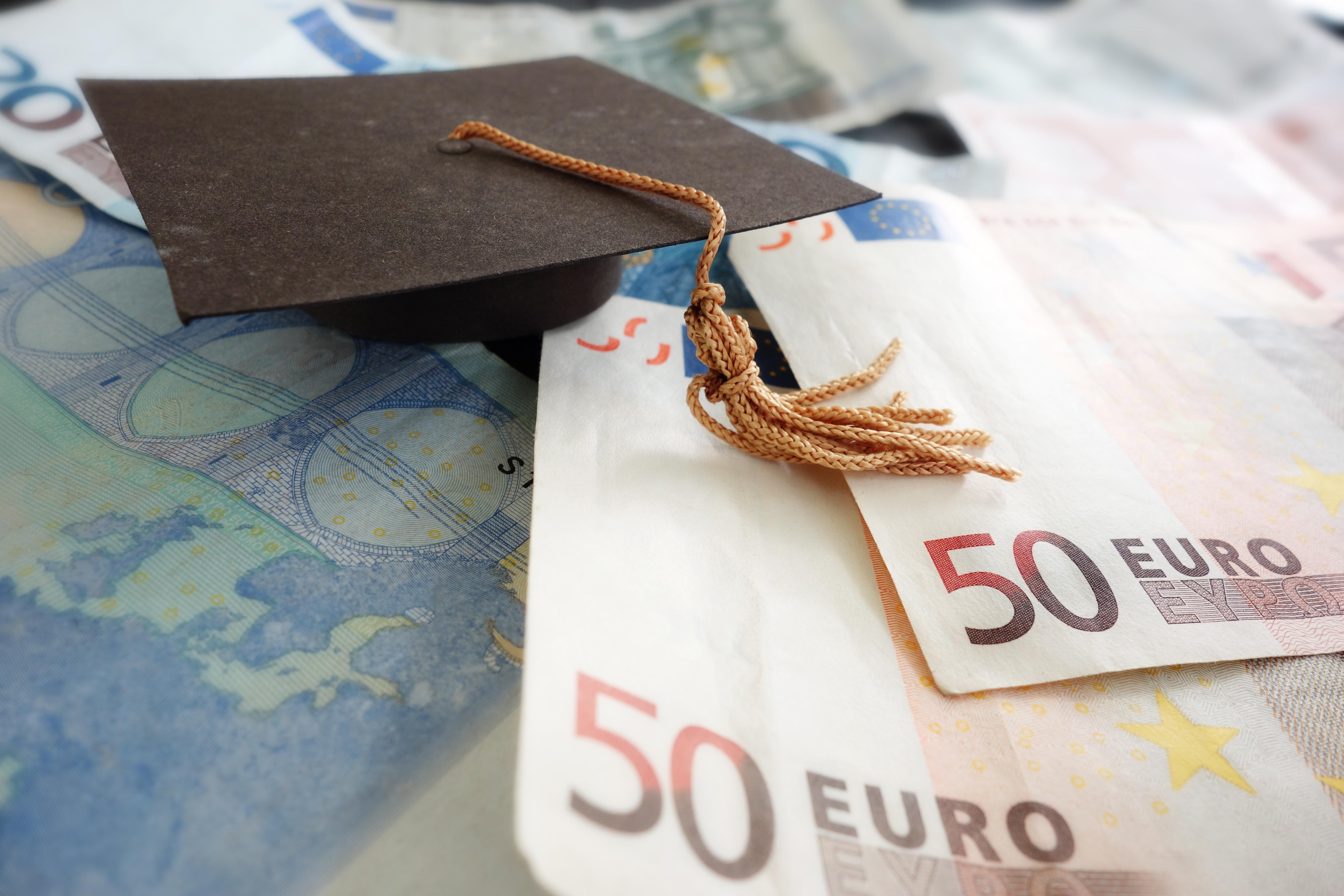 50 Euro Schein liegt auf Tisch mit Absolventenhut