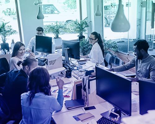 Team arbeitet zusammen in Großraumbüro