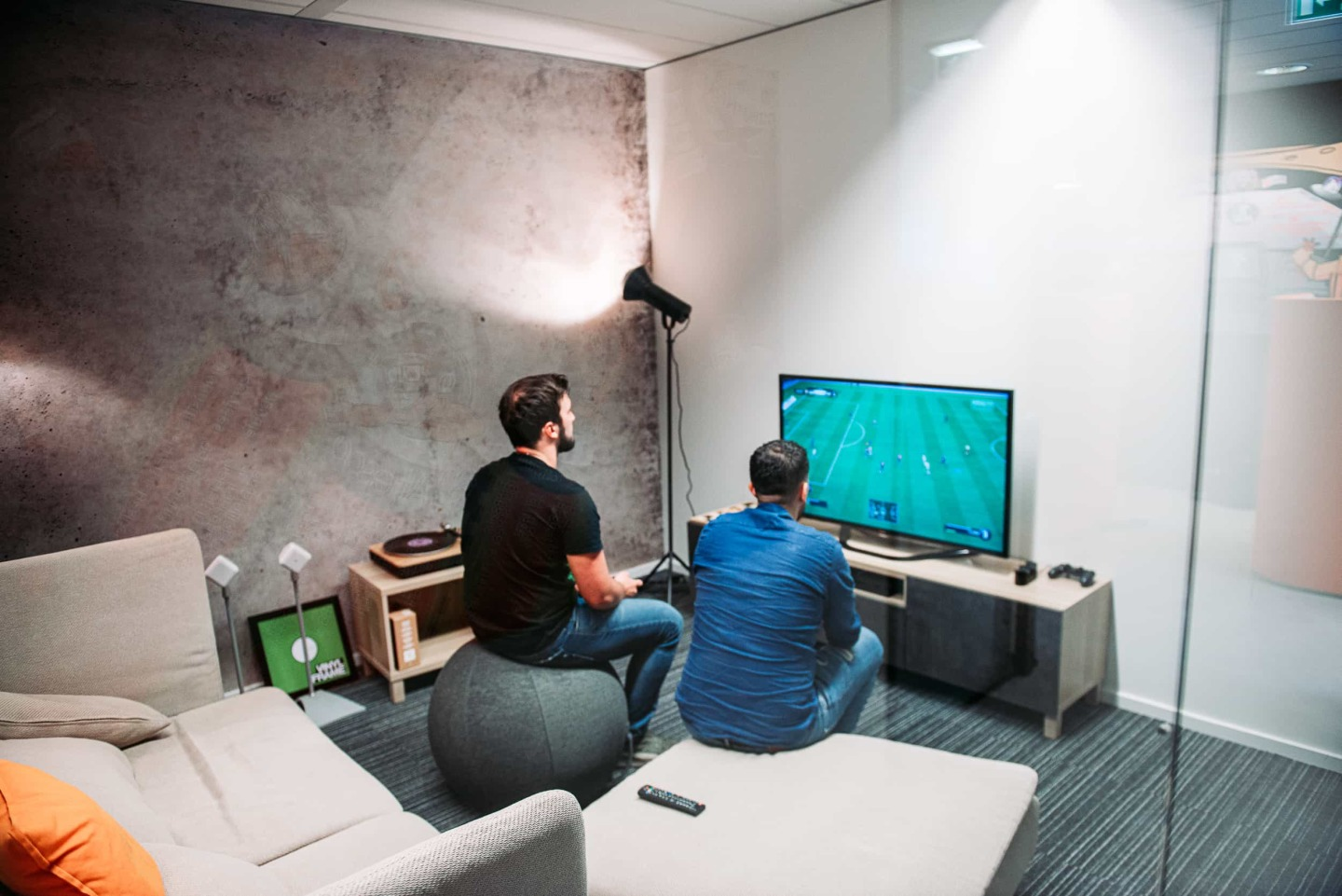 People playing FIFA in their office.