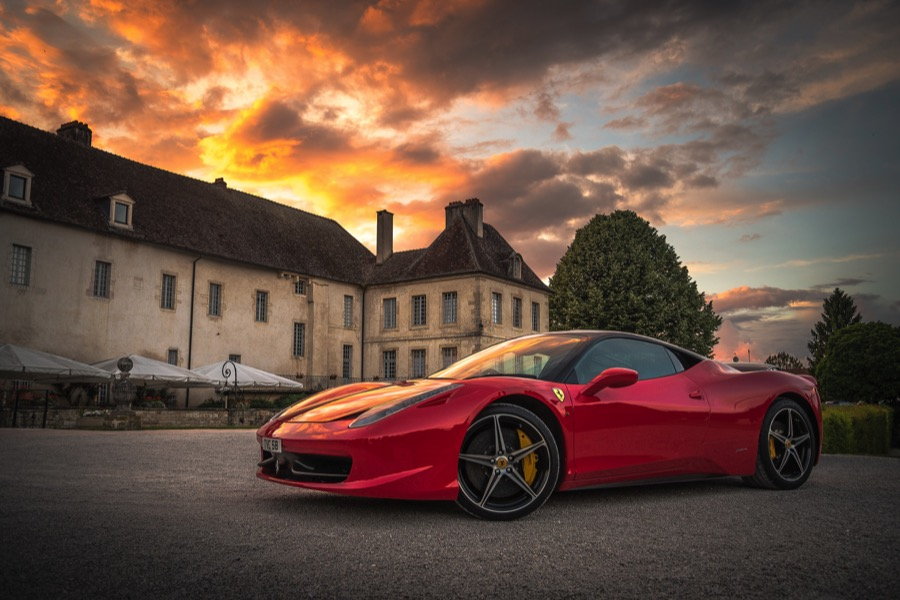 Photo of a Ferrari in front of a mansion at sunset