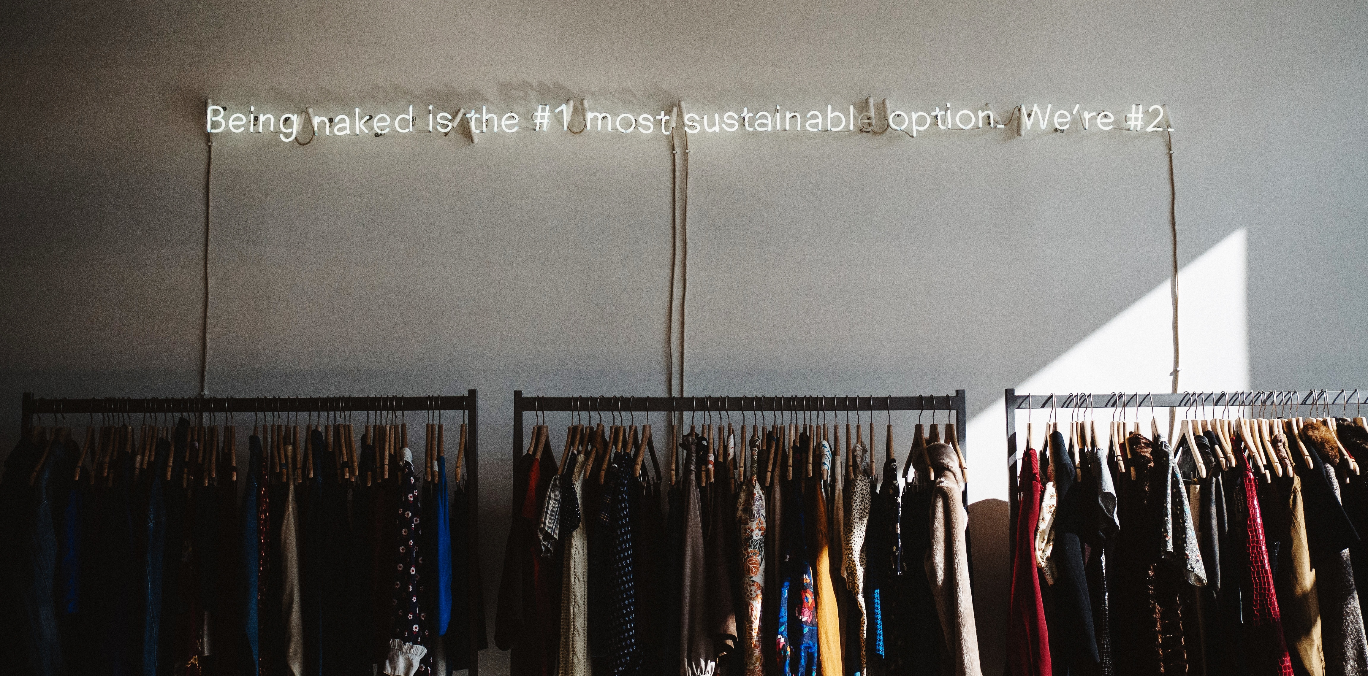 Clothes hanging neatly on rail with a light up sign above reading 'naked is the number one most sustainable option'