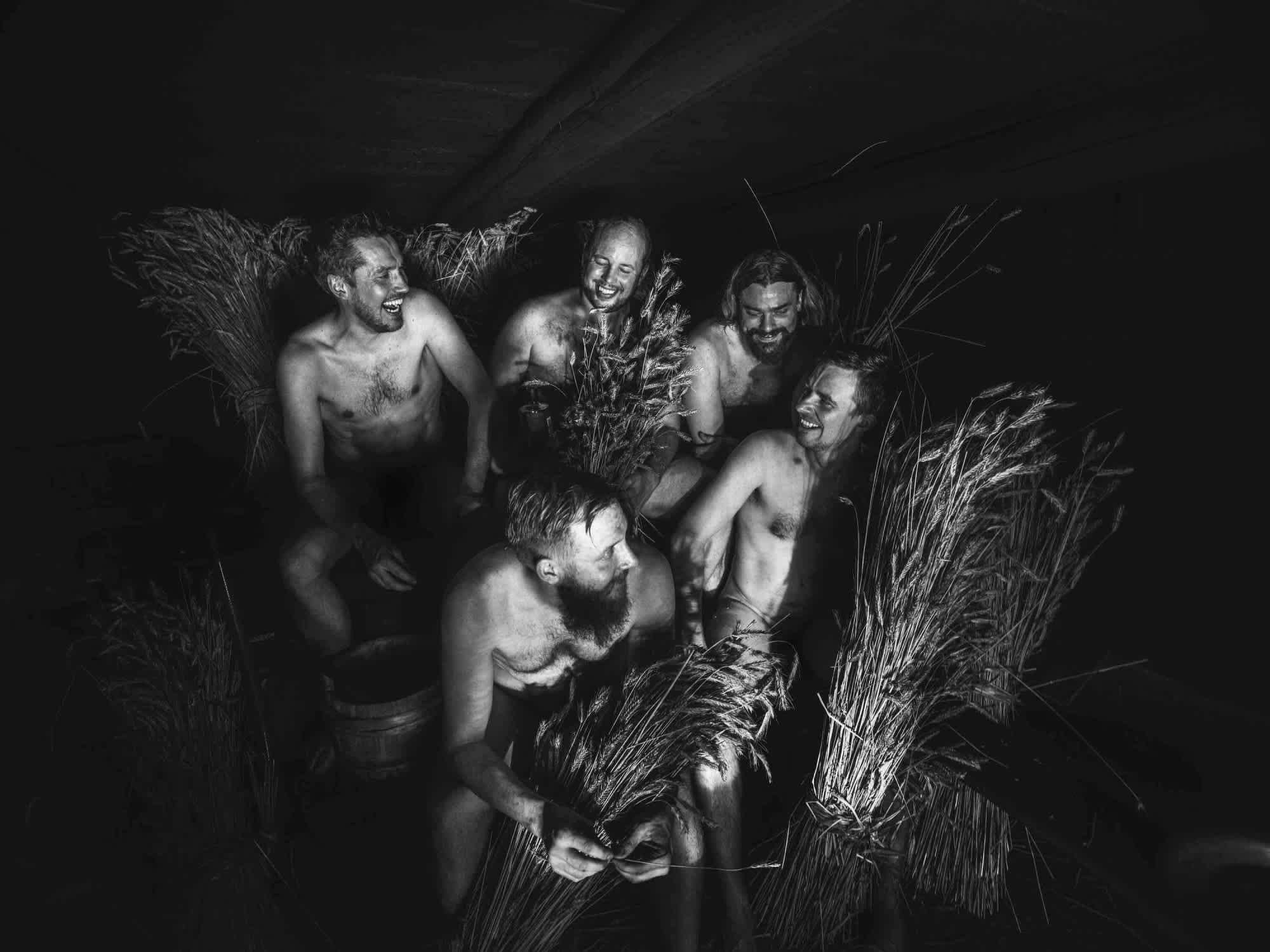 A black and white image of the five Kyrö founders sitting in a midsummer sauna surrounded by bushels of rye.
