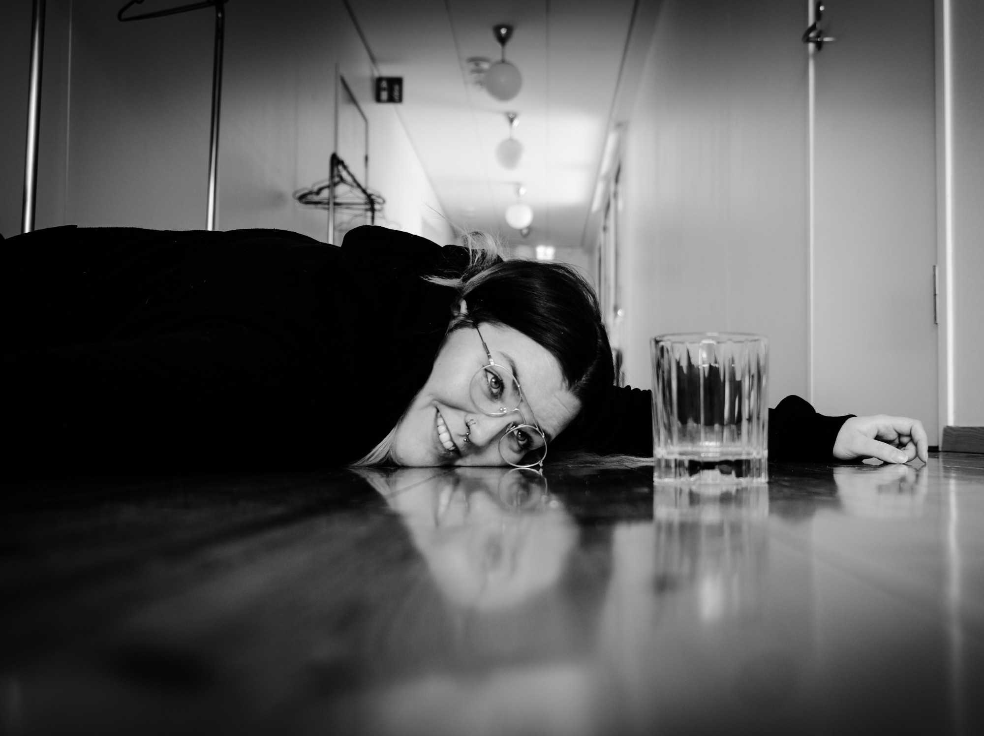Woman laying on floor staring at an empty glass.
