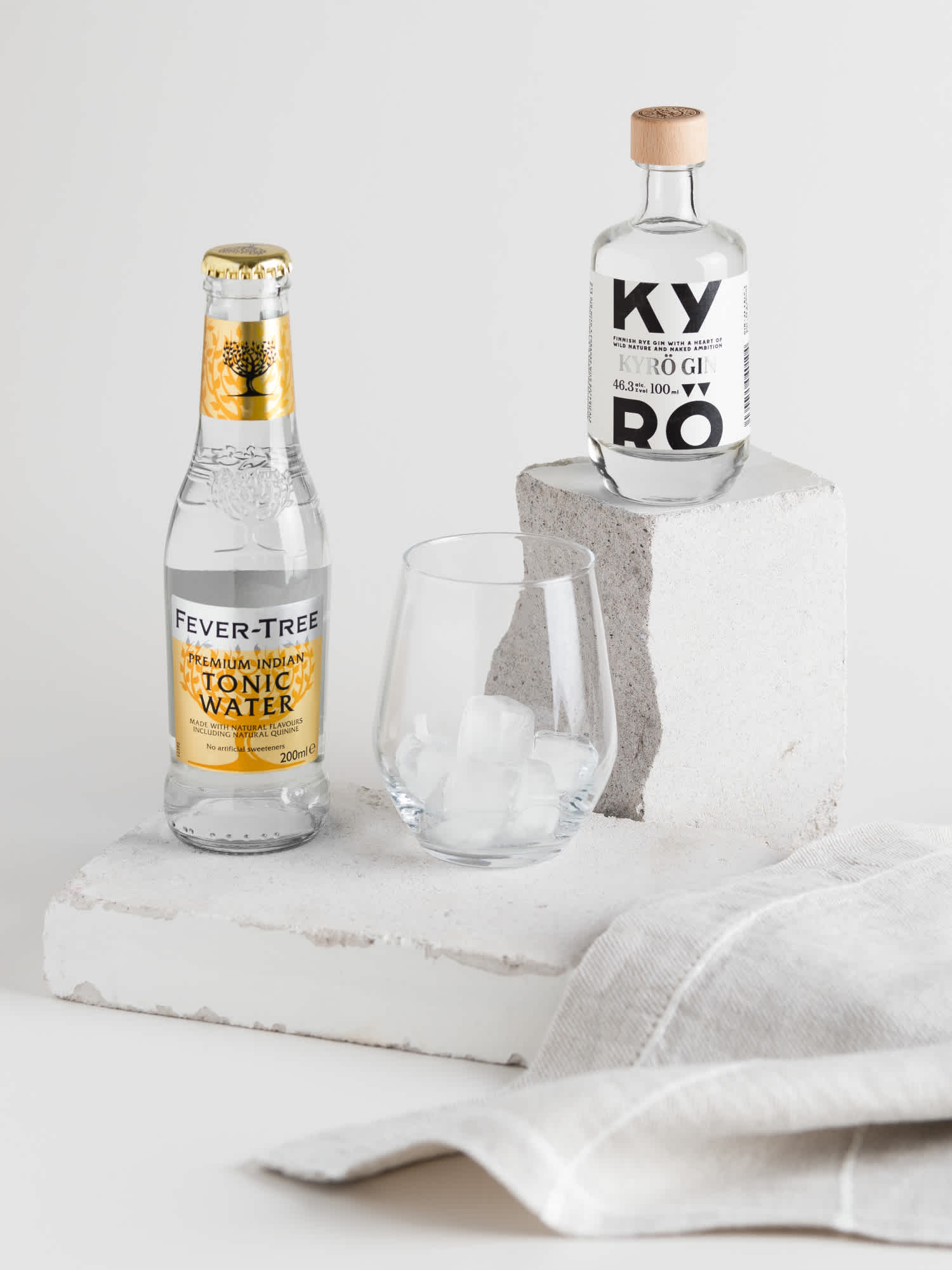 A 100 ml bottle of Kyrö Gin stands on top of a concrete block. Below it, on another concrete block, a 330ml bottle of Fever-Tree Indian Tonic stands next to a glass filled with ice. Next to that, a linen tea towel lays.