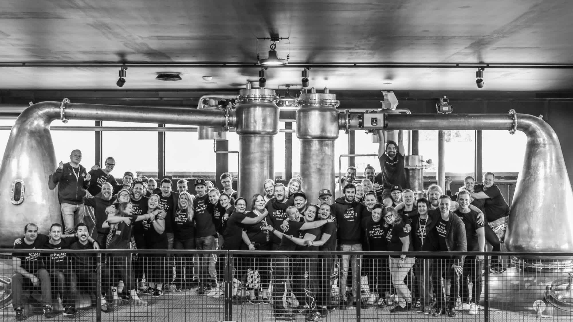 A black and white image of the Kyrö people: most of the Kyrö team pictured in front of the whisky pot distills in Isokyrö, Finland.