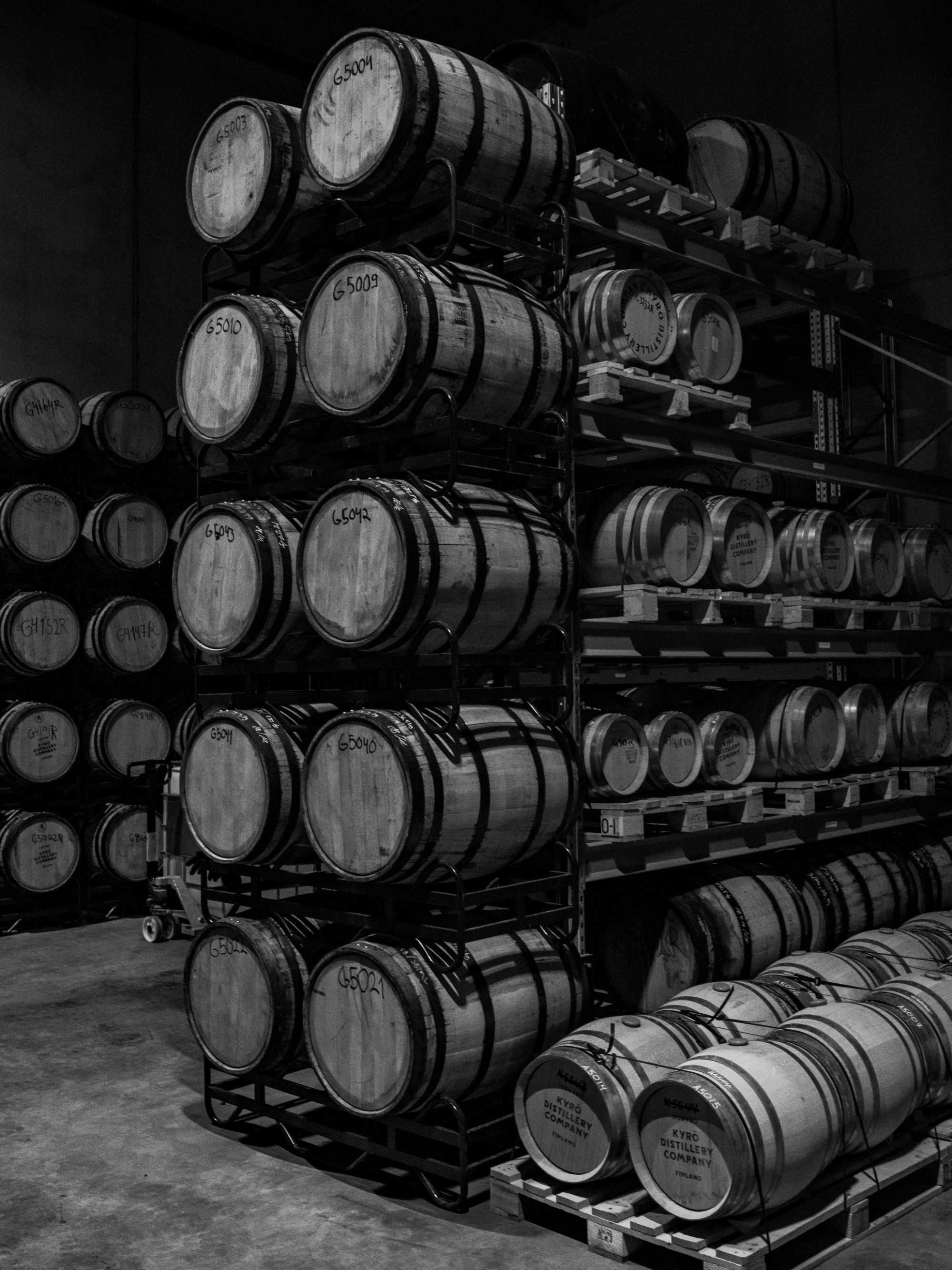 A black and white image of one of the Kyrö barrel warehouses, pictured are wooden barrels stacked atop one another.