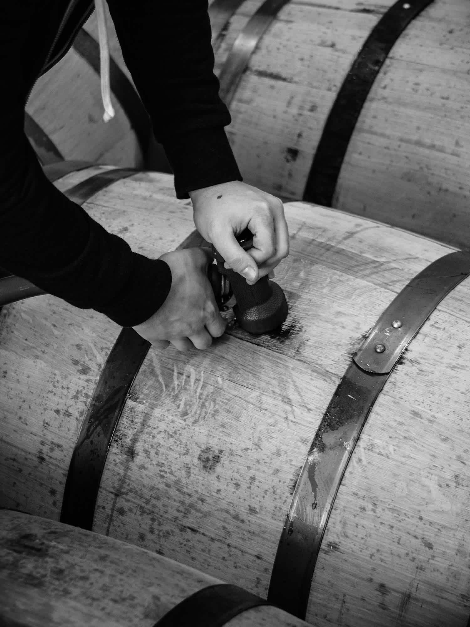 Black and white image of a person filling a barrel with alcohol