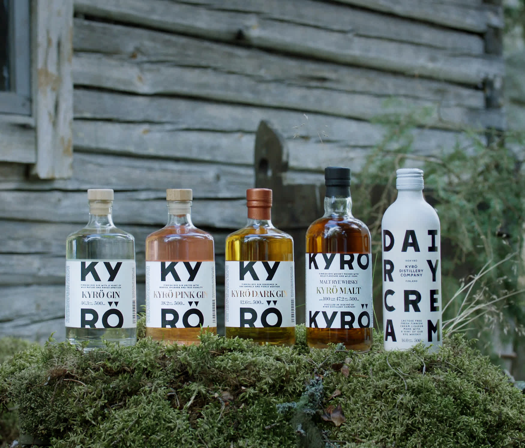 Line up of all Kyrö products including, Kyrö Gin, Kyrö Dark Gin, Kyrö Pink Gin, Kyrö Malt rye whisky and Dairy Cream cream liqueur. In the background Finnish forest.