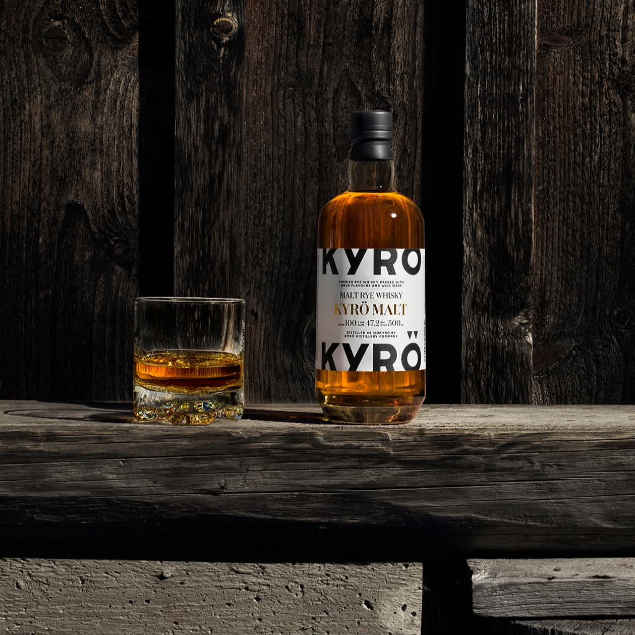 Bottle of Kyrö Malt Rye whisky and a shot of whisky neat placed on a wooden bench