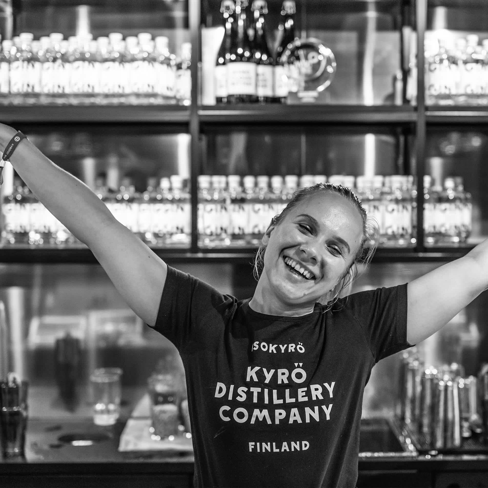 Girl standing in front of a bar wearing Kyrö Distillery t-shirt and smiling.