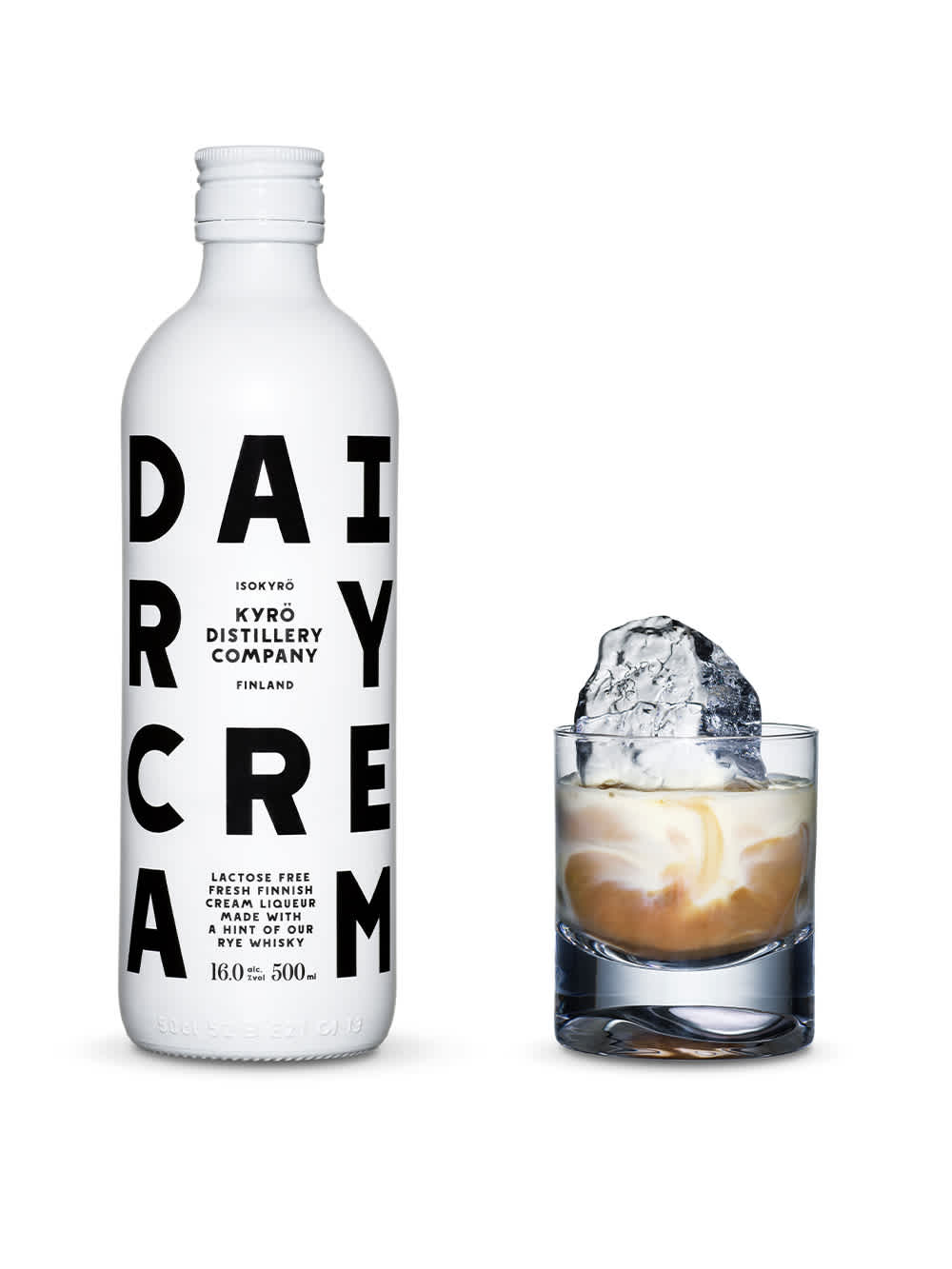 White, opaque bottles of Dairy Cream liquor with black font and Kyrö logo next to a tumbler glass filled with a shard of hand-cut ice, coffee, and Dairy Cream liquor. Produced in Isokyrö, Finnland.