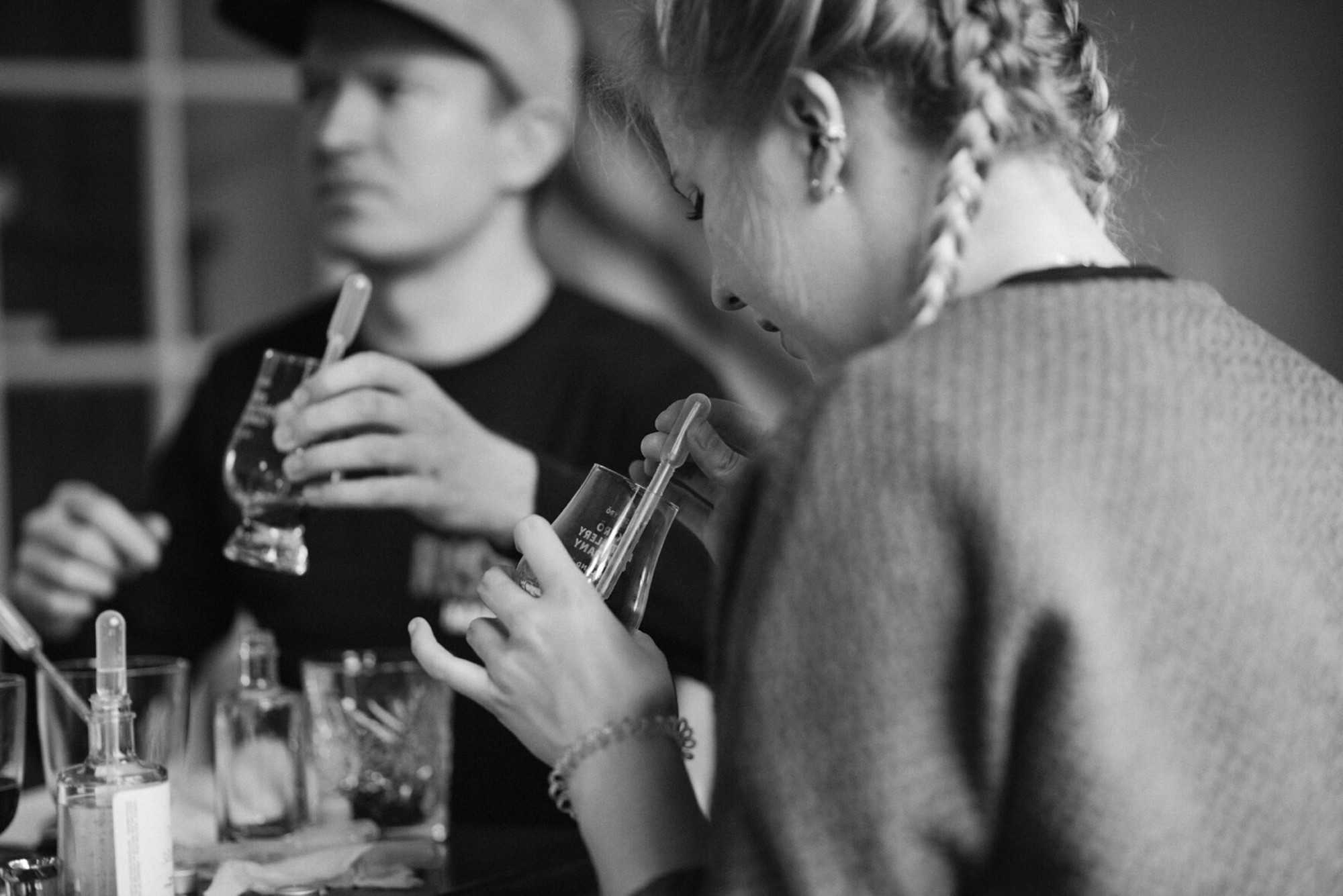 Black and white image of a man and woman attending a gin blending workshop, sniffing tasting glasses.
