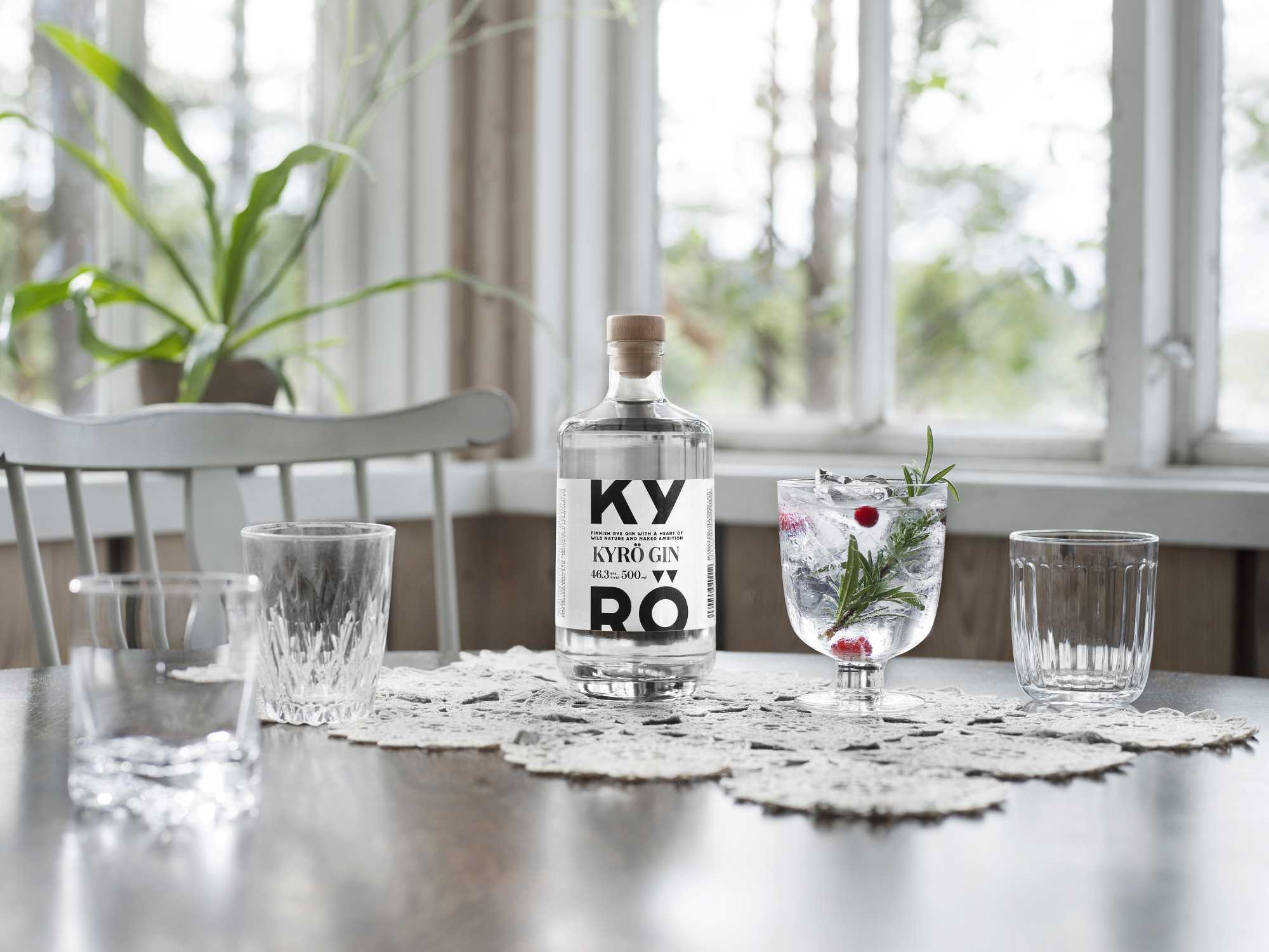 A bottle of Kyrö Gin standing on a dining table in a light-filled room next to an Iittala cocktail glass filled with Gin & Tonic, rosemary, and cranberries. Horizontal.