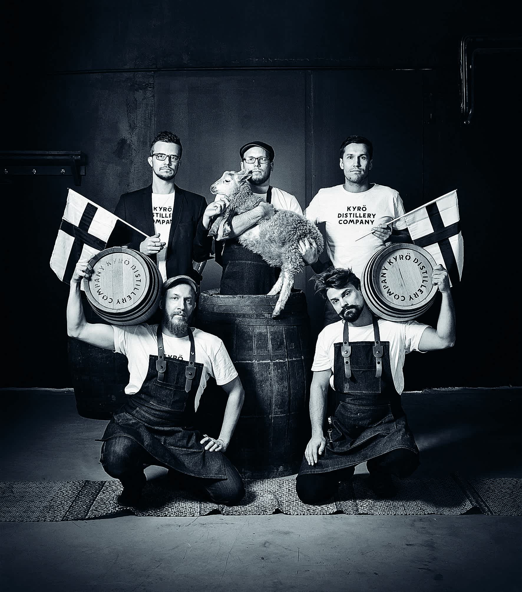 Black and white image: the five founders of the Kyrö Distillery Company in a group picture, two holding barrels, two holding Finnish flags, one holding a lamb.