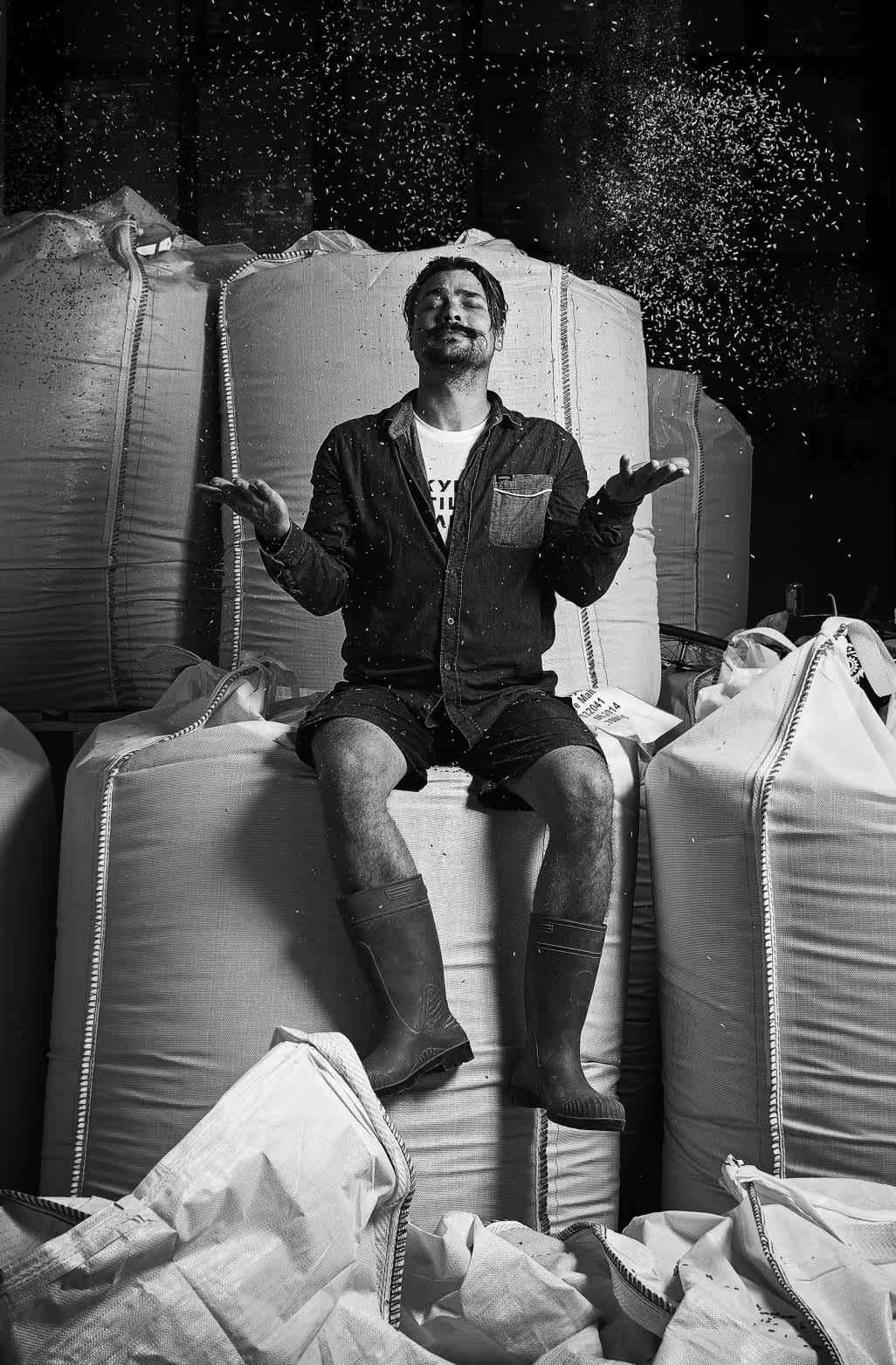 Black and white image: head distiller Kalle Valkonen sit atop bags of rye, tossing kernels into the air.